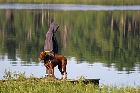 A young boy on a dock with his dog Stock Photo