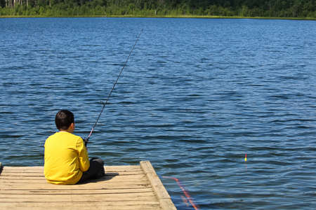 A young boy sitting on a dock and fishing Stock Photo