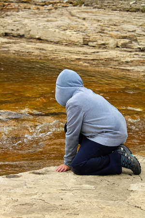 A young boy at a rivers edge watching water flowing Stock Photo
