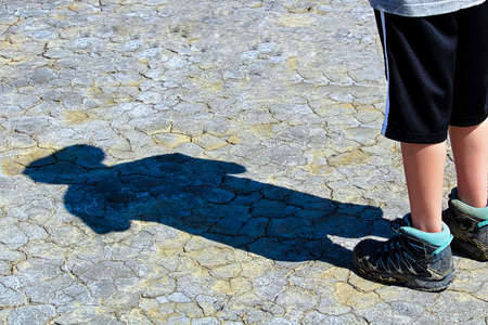 Shadow of a woung boy on dried mud