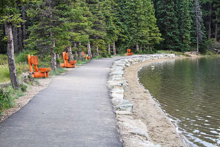 A path lined with wooden benches by a lake shore Stock Photo