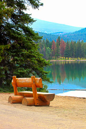A rustic bench sits on a calm lake shore in the mountains