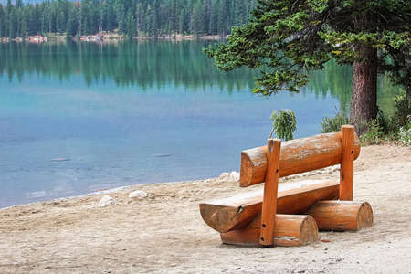 A rustic bench sits on a calm lake shore Stock Photo