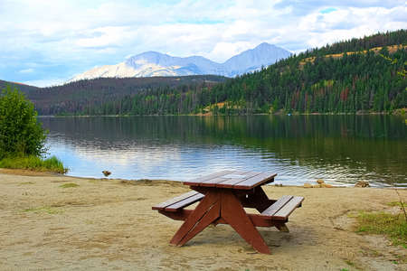 An empty picnic table on the edge of a mountain lake
