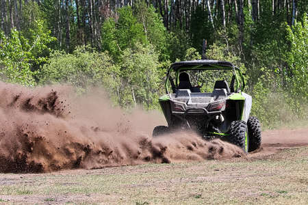 A side-by-side ripping up dirt as it turns a corner