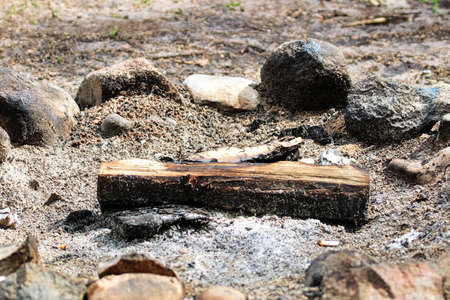 An unburnt log in a fire ring