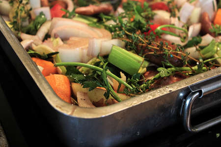 The corner of a roasting pan full of vegetables and herbs.