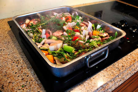 A roasting pan full of vegetables and herbs steaming. Stock Photo