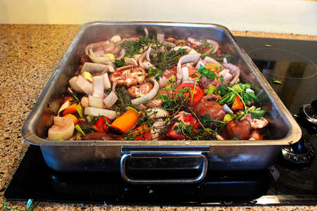 Sauteing a roasting pan full of vegetables and herbs.