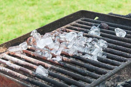 Ice cubes melting on a barbeque grill Stock Photo