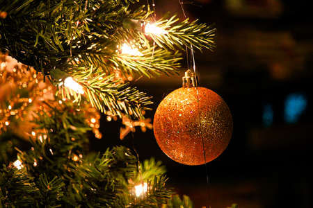 A sparkly Christmas ball ornament against a dark background
