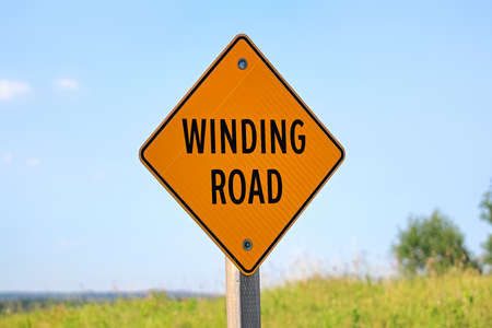 A winding road sign against a blue sky