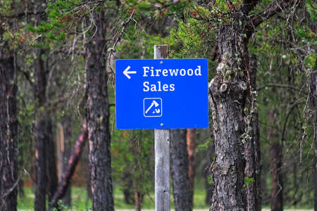 A blue firewood sales sign with a directional arrow