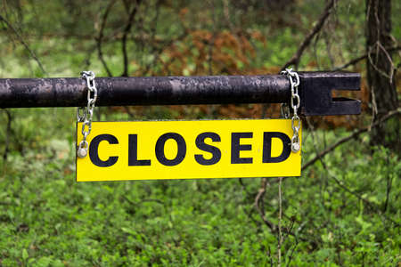 A yellow closed sign on an metal gate