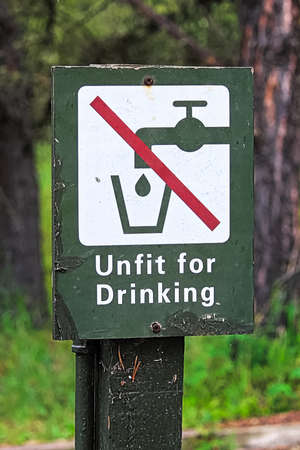 A green unfit for drinking water sign