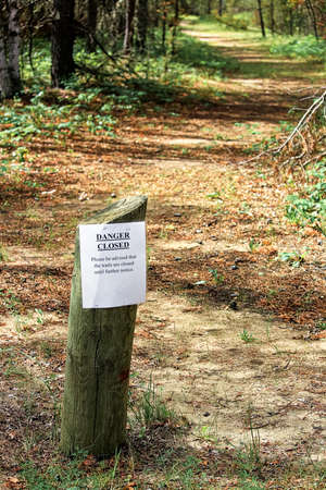 A trails closed sign with a path in the background