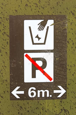 Closeup of a garbage and no parking in-front sign