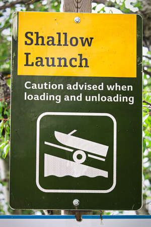 A shallow boat launch sign advising caution Stock Photo