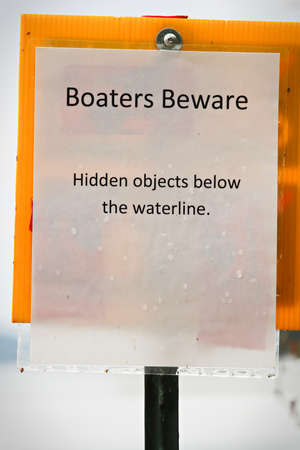 A boaters beware hidden object under water sign