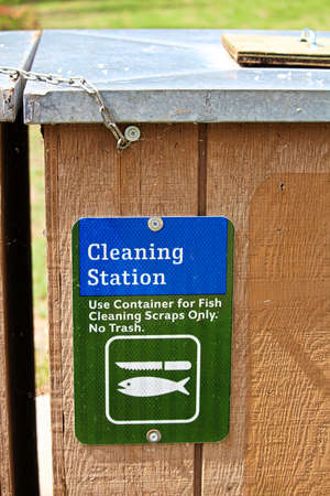 A cleaning station sign indicating container only for fish scraps