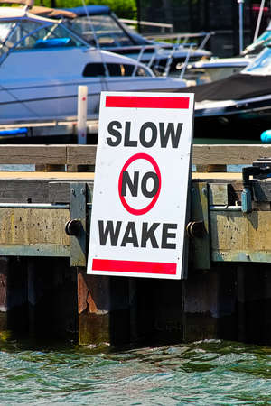 A slow no wake sign on a dock with boats in the background Stock Photo