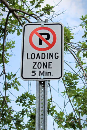 A no parking, five minute loading zone sign.