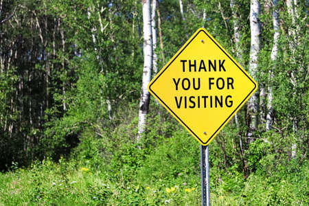 A thank you for visiting sign against a forest background.