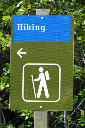 A blue and green hiking direction sign with an arrow.