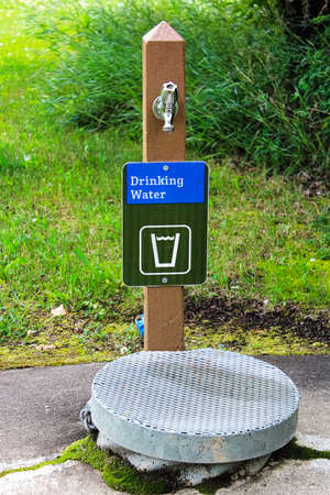 A drinking water sign next to a well cover.