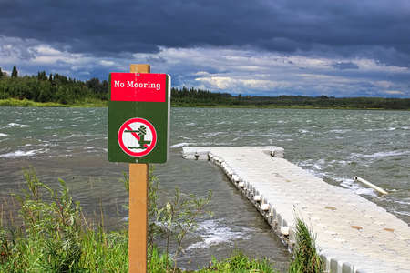 A red no mooring sign beside a floating dock during a storm.