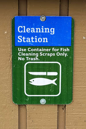 A cleaning station sign indicating container only for fish scraps. Stockfoto