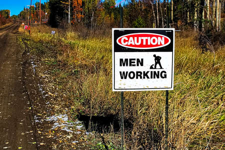 A caution men working sign beside a road.