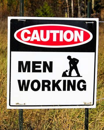 Closeup of a caution men working sign.