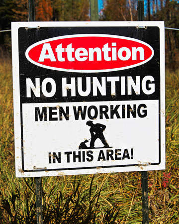 An attention no hunting, men working sign.