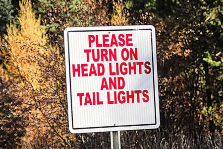 A sign indicating to turn on all vehicle lights. Stock Photo