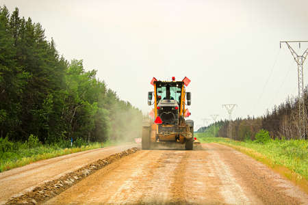 Traveling on a gravel road behind a grader