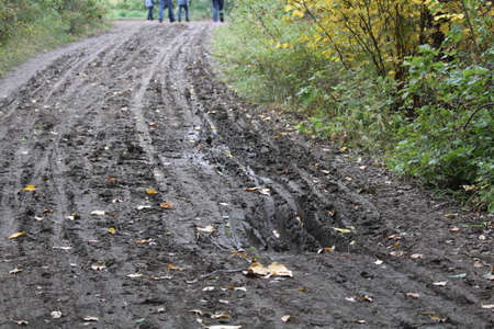 Closeup of a muddy rut in a road with people walking in the background