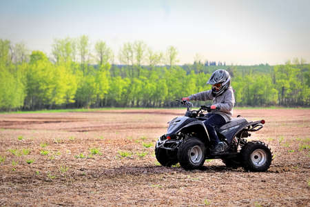 A young boy quading in a spring field.