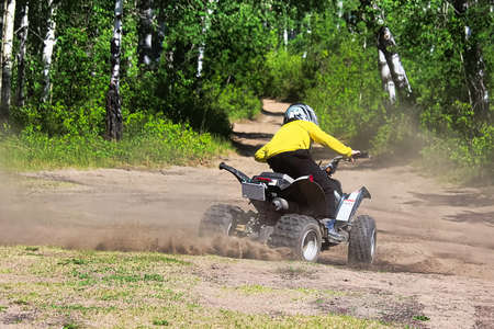 A young boy on a quad does spins in the dirt. Banco de Imagens