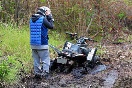 A young boys holds his helmet looking at his stuck quad.