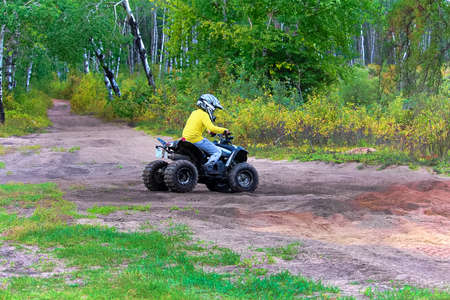 A young boy drives his quad on sandy ground.