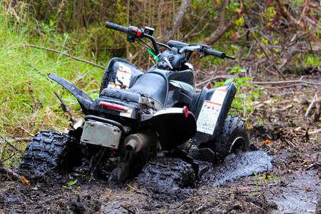 Closeup of a quad stuck in mud.