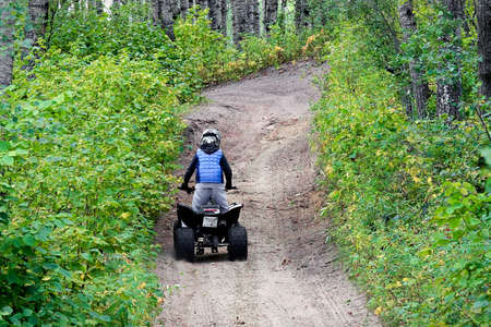 A young boy quads up a hill through the forest.