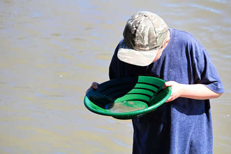 A young boy looks into a gold pan searching for treasure.