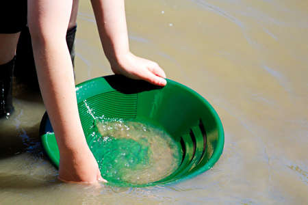 Young hands gold panning with a green pan.