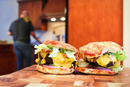 Two keto burgers sit on a table with a blurred kitchen and man in the background. Banco de Imagens
