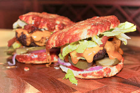 Closeup view of two messy keto burgers on a wooden board. Banco de Imagens - 119273527
