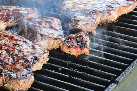 Closeup of steaks cooking on a BBQ