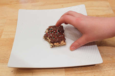 A childs hand grabing a treat off a white plate