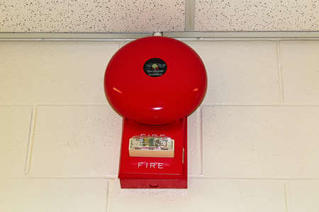 A red fire alarm hanging on a white brick wall